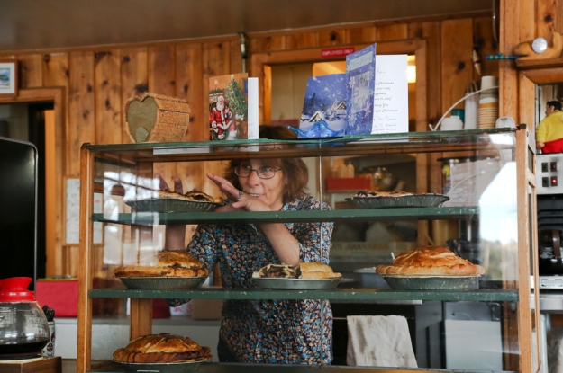 Michele Bingham, who has been serving pies at The Good Pie Cafe for eight years, grabs a pie from the rack on Dec. 18.