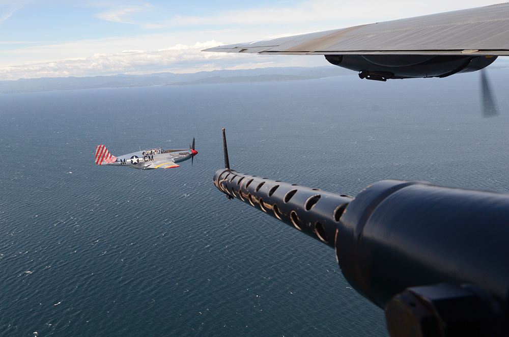 A gun turret in a B-24 Liberator points at a P-51 Mustang flying over Puget Sound on June 19, 2013. The Collings Foundation owns the planes and gives people rides in refurbished war planes to teach them about WWII history.