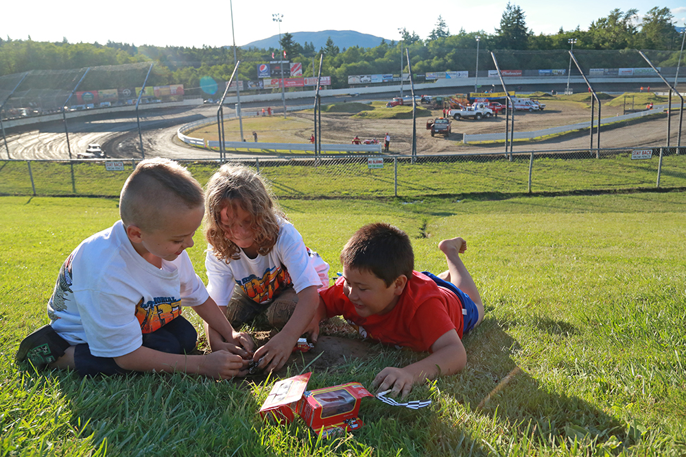 (From Left) RJ Barnes, Joshua Jackson and Christopher William-Huble race toy sprint cars in a mini dirt speedway they created. The 42nd Dirt Cup at Skagit Speedway brought racers and fans from all over the country, and even Canada. Although races on June 20, 2013 were cancelled due to rain, the sun came out for races on June 21.