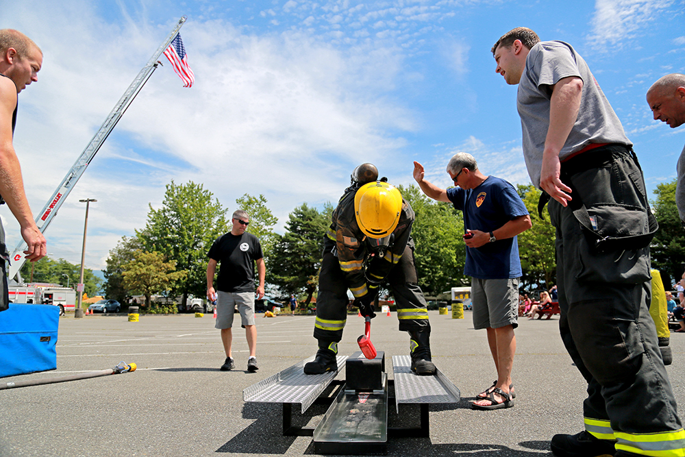 Teammates cheer on Adam Griffith from the Port of Seattle as he swings a dead blow hammer to pound a sled about five feet, simulating a forced entry with an ax. Griffin won the final round of the individual race at the Firemen's Muster in Sedro-Woolley, Wash. on June 29, 2013 with a time of 1:57. Brooke Warren / Skagit Valley Herald