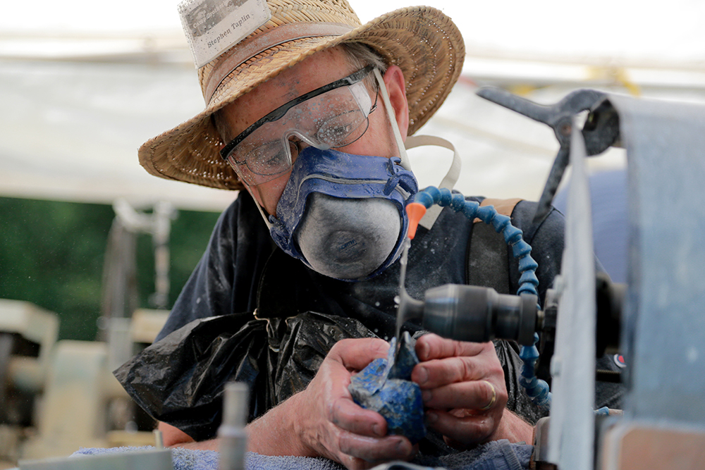 Stephen Taplin carves a bird out of lapis lazuli, a blue stone from Chile, at the Stone Carving Symposium at Camp Brotherhood on July 16, 2013. He estimated it would take him an entire day to complete the sculpture.  Brooke Warren / Skagit Valley Herald