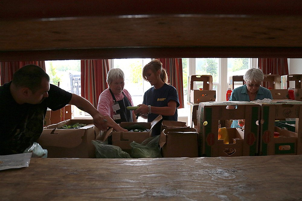 "(From left) Food bank volunteers Dave Morales, Lois Angle, Tami Metz and Jane Mayer pack boxes to deliver to families with hungry school age children on July 17, 2013. The ""Backpack Direct"" is one of the Mount Vernon Neighbors in Need Food Bank programs.  Brooke Warren / Skagit Valley Herald"