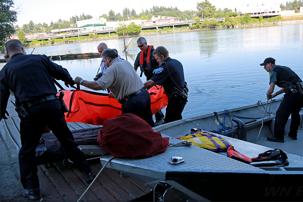 Members of the Mount Vernon Police Department and the Skagit County Sheriff's Department retrieve a body from the river on July 18, 2013 near the Moose Lodge in Mount Vernon, Wash. Brooke Warren / Skagit Valley Herald