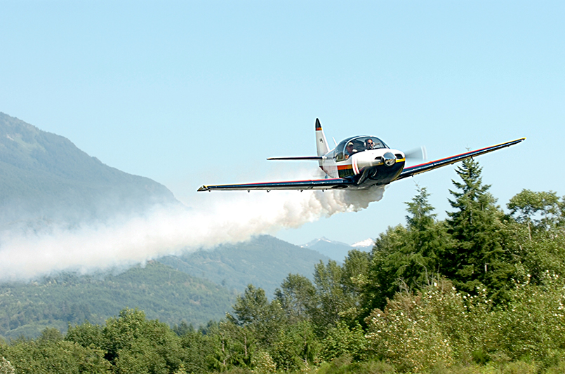 A 1946 Globe GC-1A leaves a smoke trail as it flies over Mead Field at the Concrete Airport for the North Cascades Vintage Fly-In on July 19, 2013. Brooke Warren / Skagit Valley Herald
