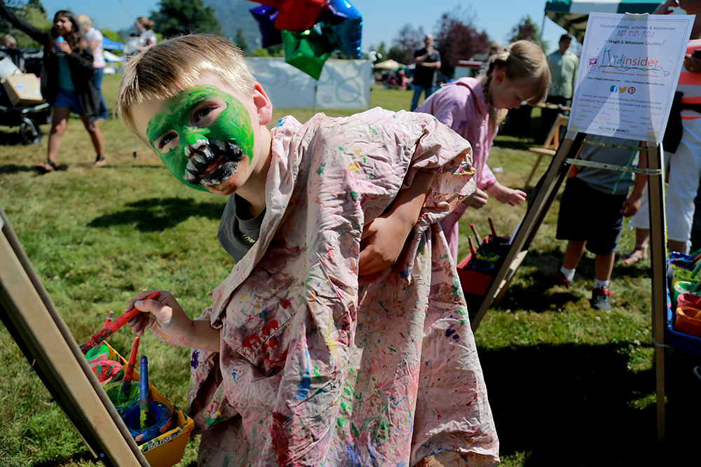 Gavin St. Clair adjusts his oversized smock while he paints at the Children's Art Festival on July 20, 2013 in Hillcrest Park in Mount Vernon, Wash. He was incognito as a T-Rex while exploring the festival.  Brooke Warren / Skagit Valley Herald