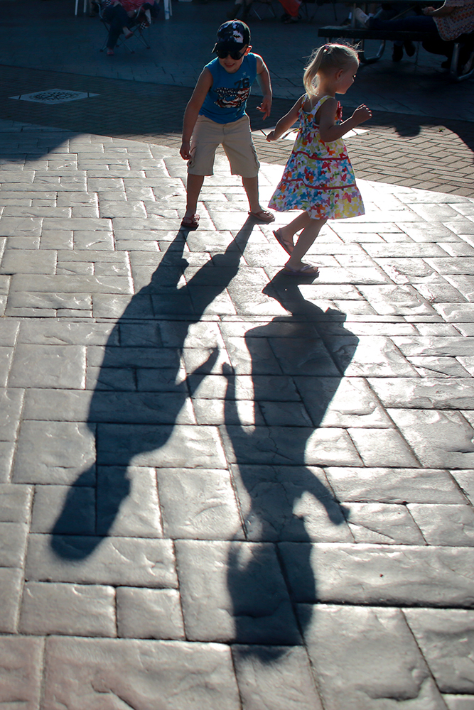 Conner and Lily Schulthess watch their shadows as they dance to the Troy Fair Band at the Loggerodeo Street Dance on July 3, 2013 in Sedro-Woolley, Wash.  Brooke Warren / Skagit Valley Herald