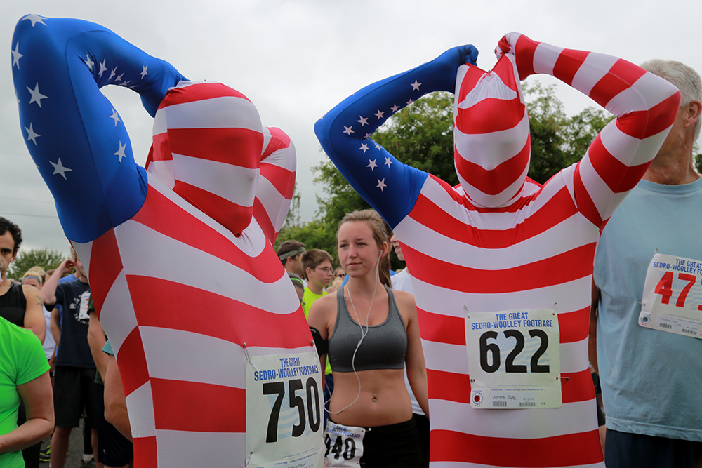 "Ryan Welch (left) and Joe Jones pull the hoods of their patriotic morphsuits over their heads before starting the Great Sedro-Woolley Footrace on July 4, 2013. ""It's almost being naked, but not,"" Jones said.  Brooke Warren / Skagit Valley Herald"