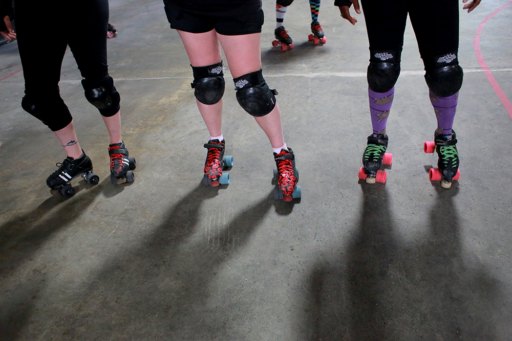 "Team members of the Skagit Valley Roller Derby team stand on their track before practicing blocking a ""jammer,"" the opposing team's member who scores points.  Brooke Warren / Skagit Valley Herald"