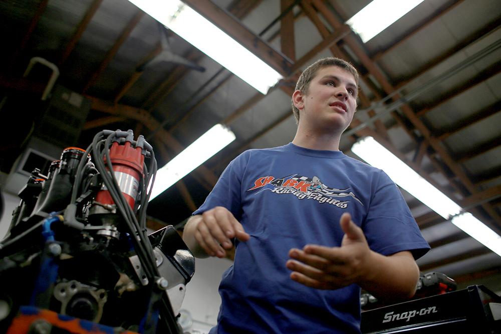 Mack Brown explains the parts of a sprint-car engine at Shark Racing Engines in Sedro-Woolley, Wash. where he works. He has learned a lot from the shop owner, Marc Huson, about rebuilding racing engines, which he puts to use for his own racing career.  Brooke Warren / Skagit Valley Herald