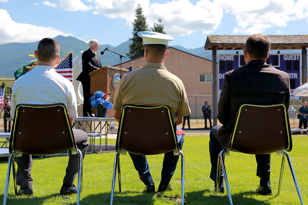 (From left) Paul Rider, political affairs coordinator for Patriot Day; Maj. Jason Vose, Douglas Vose's brother; and Michael Frank, Douglas Vose's best friend through childhood, listen to former U.S. Defense Secretary Robert Gates at Patriot Day on July 27, 2013 in Concrete, Wash. The event was to honor Douglas Vose III, a Green Beret who lost his life in 2009 in Afghanistan. Brooke Warren / Skagit Valley Herald