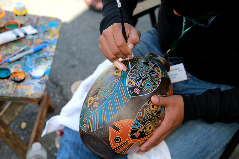 Luis Enrique Gutierrez paints in a thin groove on a traditional Nicoya style pot at the Anacortes Art Festival on Aug. 3, 2013. He uses stone burnishing to achieve the smooth finish on his pottery. Brooke Warren / Skagit Valley Herald