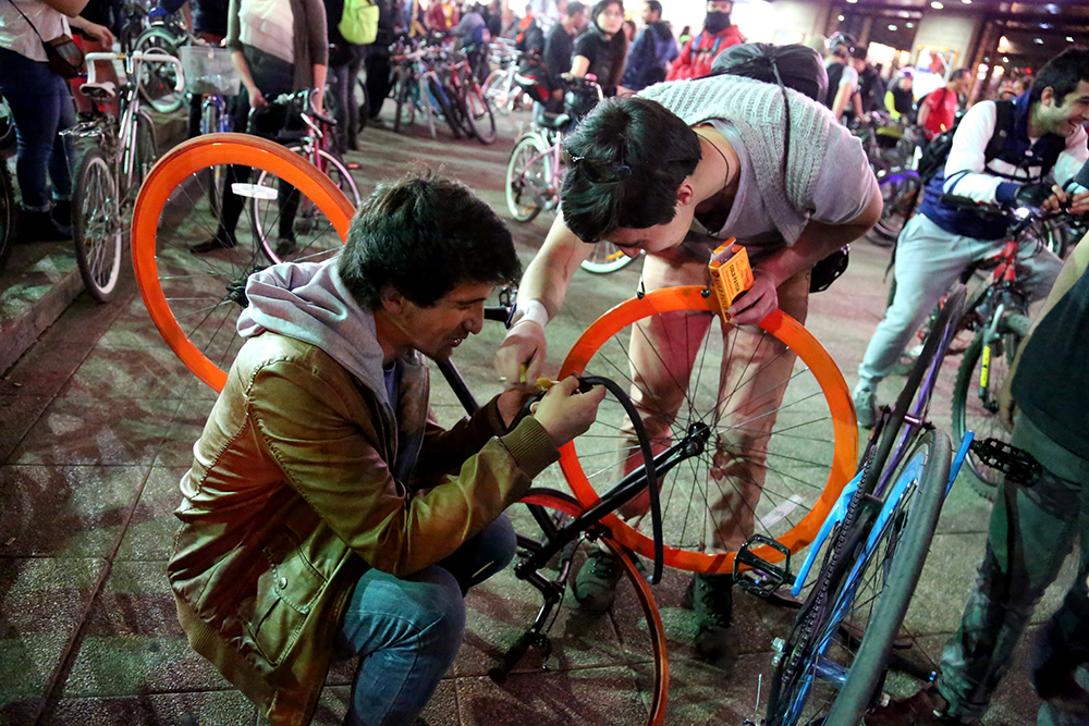 "Diego Cortes (left) and Jaime Yavara patch a tire on Sept. 3, 2013 before a ""cicletada."""