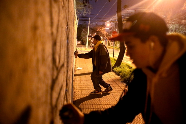 (From left) Julian Gaona, 13, and Nicholas Douglas, 14, paint graffiti on a temporary wall surrounding construction on Sept. 6, 2013 in Santiago, Chile.