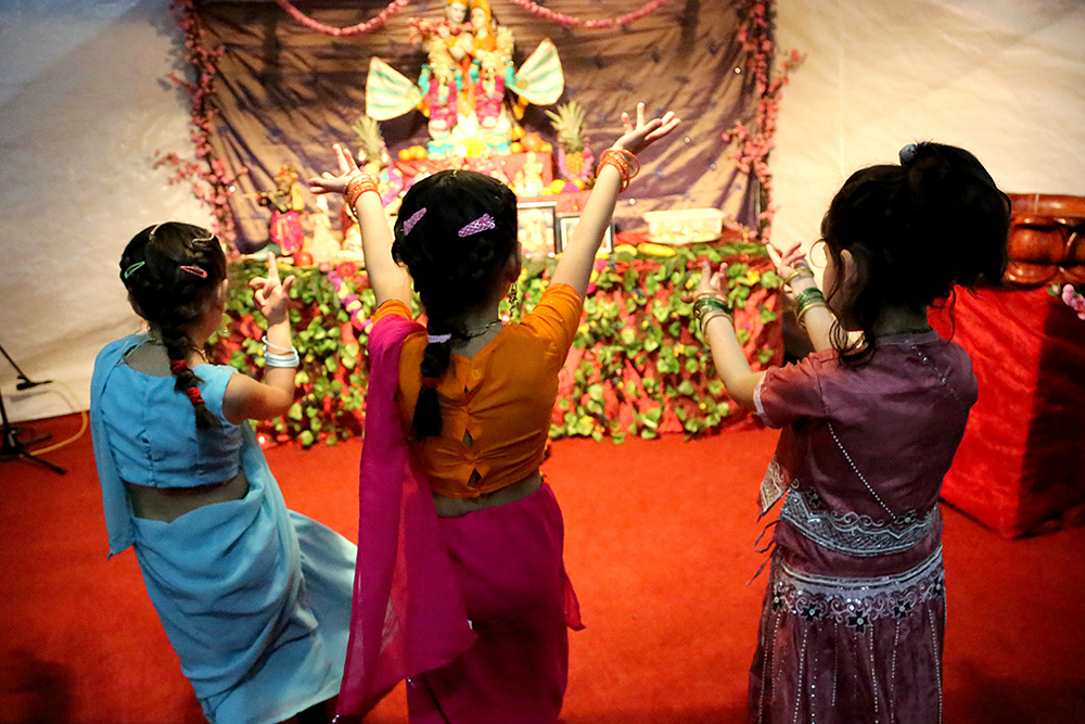 (From left) Sachi, Anandini and Goura dance in front of an alter for Krisha. Hundreds of people gathered to celebrate the Janmastami Festival that commemorates the birth of the Hindu god Krishna on August 28, 2013 at Hare Krishna Temple in Santiago, Chile.