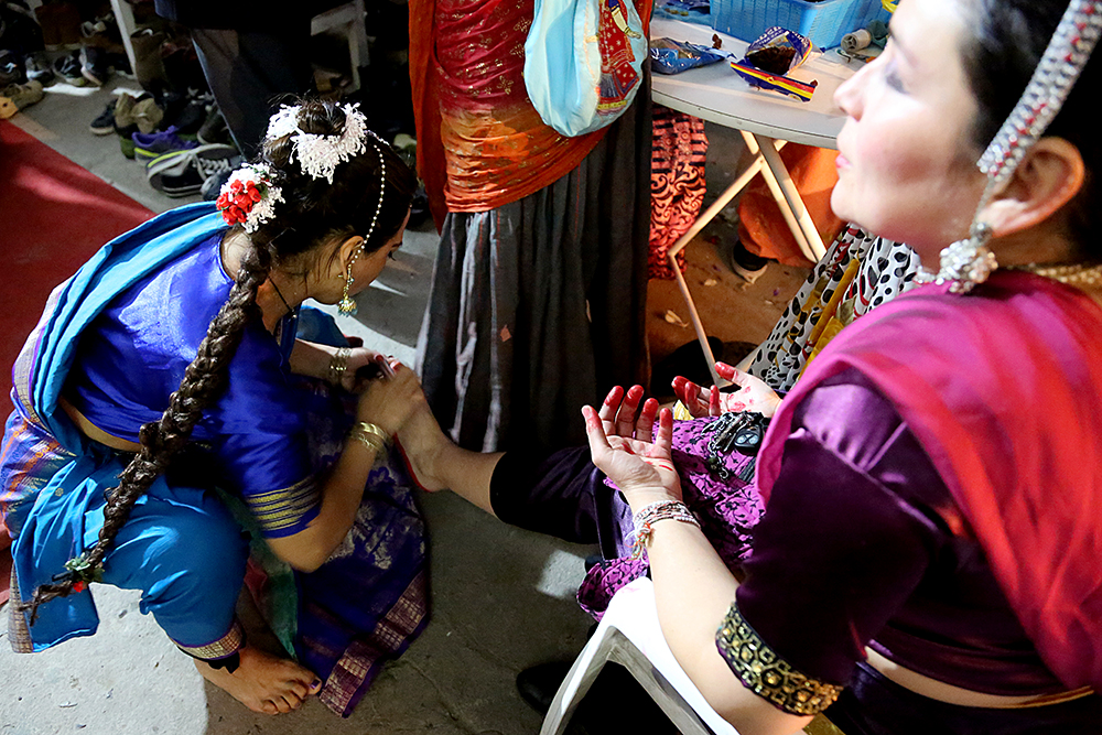 Adriana Waikinao paints Loreto Millalen's feet with lipstick to mimic henna before they perform a dance. Hundreds of people gathered to celebrate the Janmastami Festival that commemorates the birth of the Hindu god Krishna on August 28, 2013 at Hare Krishna Temple in Santiago, Chile.