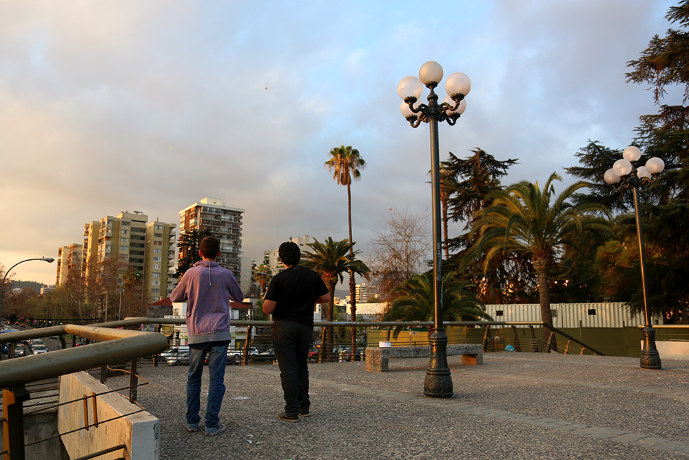 (From left) Renato Molina, 14, and José Reyes, 14, fly kites on Sept. 9, 2013 on the sky bridge at Plaza Pedro de Valdivia in Santiago, Chile. Flying kites is a popular hobby in Chile, and more people come out with strings and wings during the warmer months.