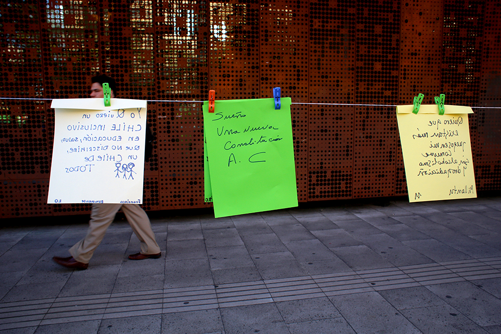 Supporters for Michelle Bachelet, the Socialist candidate for Chile's 2013 presidential election, created a line of wishes for Chile's future outside GAM, Gabriela Mistral Cultural Center, in Santiago on Oct. 3, 2013. They invited anyone walking along the street to add their wishes for Chile. Many wishes included a new constitution and free education for all.