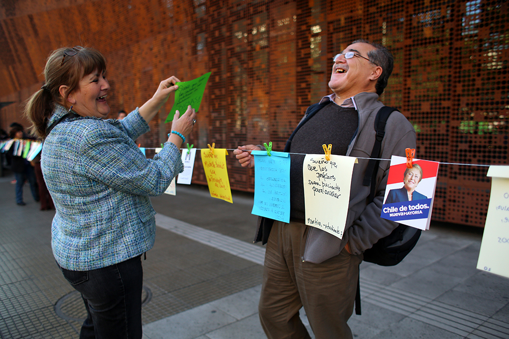 Mladenka Sanchez and Carlos Muñoz share a laugh of relief after Sanchez recovers her wish for Chile that had blown into the street. Supporters for Michelle Bachelet, the Socialist candidate for Chile's 2013 presidential election, created a line of wishes for Chile's future outside GAM, Gabriela Mistral Cultural Center, in Santiago on Oct. 3, 2013. They invited anyone walking along the street to add their wishes for Chile.