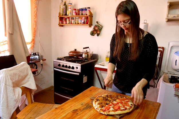 Dora Nuss-Warren makes pizza at her home in Los Antiguos, Argentina. Her home also serves as a DVD Rental shop and an English classroom.