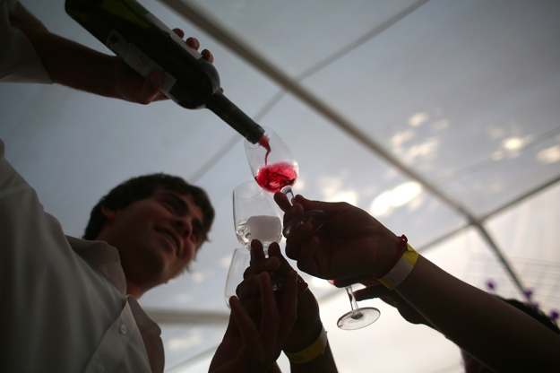 A server pours the last drops of wine as attendees wrestle to have it in their glass at the Santa Julia vineyard's 15th Annual wine-tasting event on Nov. 16, 2013 near Mendoza, Argentina.