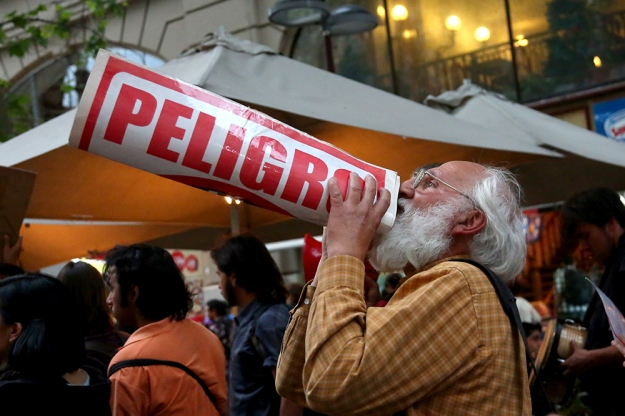 A protester chants through a sign at a demonstration in central Santiago, Chile on Oct. 24, 2013.