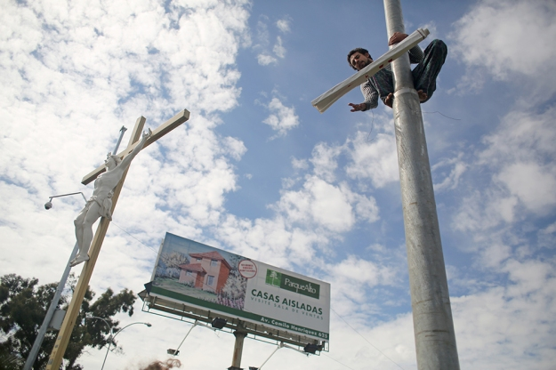 Chagul Orrego climbs a light pole to unfurl a sign in protest of a hydroelectric plant in Cajón deMaipo, a rural suburb in Santiago, Chile on Sept. 7, 2013. The hydroelectric plant would destroy the ecology in the canyon, but it would also bring jobs to the people living there, Orrego says.
