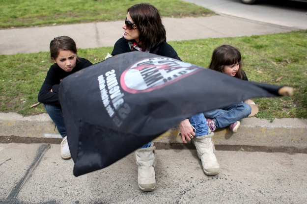 "A woman waves a flag with her children at a ""No Alto Maipo"" protest."