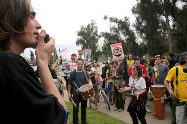 "Anthony Prior, left, leads protestors in a chant on Sept. 7, 2013. ""Luksic, cagón, fuera del cajon!"" they shout. Luksic is one of the wealthiest families in Chile and they are funding the hydroelectric development."