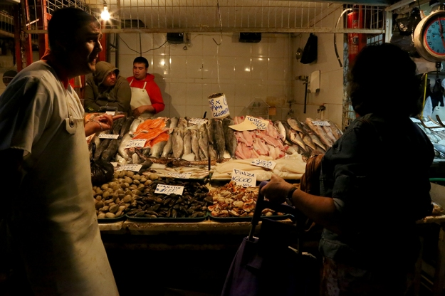 Vendors at a fish market in Santiago, Chile chant their prices and hail customers to buy their seafood. They keep the fish for up to five days, while periodically laying it on fresh ice, before it is no longer deemed fresh. Seafood is part of the traditional Chilean diet due to the country's easy access to the Pacific Ocean.
