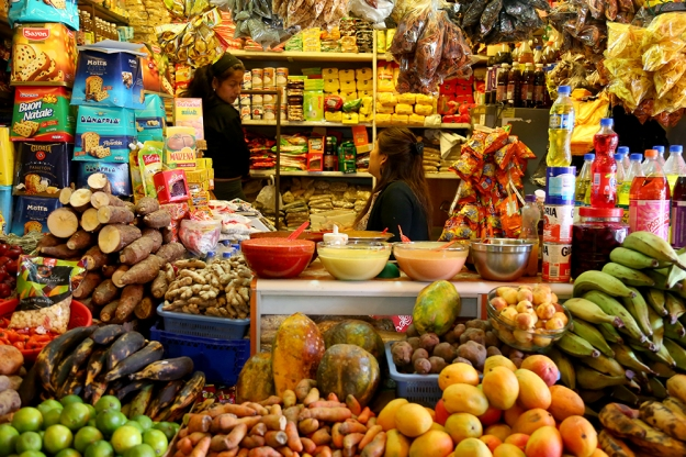 Women sell a variety of foods in their stalls at a traditional market in Santiago, Chile. Many Chileans shop at supermarkets, but open-air markets are still popular, especially to buy produce.