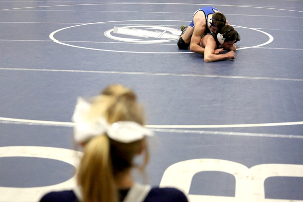 Adam Adkinson from Sedro-Woolley High School and Luke Jordan from Squalicum High School wrestle with cheerleaders watch from the sidelines. High School wrestlers competed in the boys 2A regional wrestling tournament on Feb. 15, 2014, at Squalicum High School in Bellingham, Wash.
