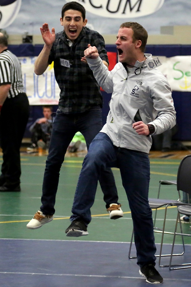 Head coach Russ Robinson and volunteer coach Wren Bishop celebrate Luke Jordan's victory in the 120 weight class at the boys 2A regional wrestling tournament on Feb. 15, 2014, at Squalicum High School in Bellingham, Wash.