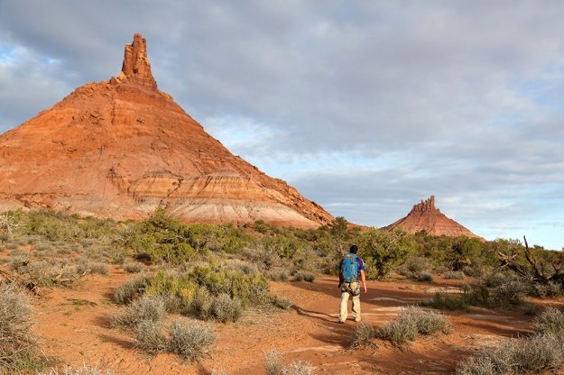 Morgan Foster approaches South Six Shooter on the morning of March 28, 2014. South Six Shooter and North Six Shooter, in the background, are two solitary towers that stand northwest of the cragging buttresses in Indian Creek.