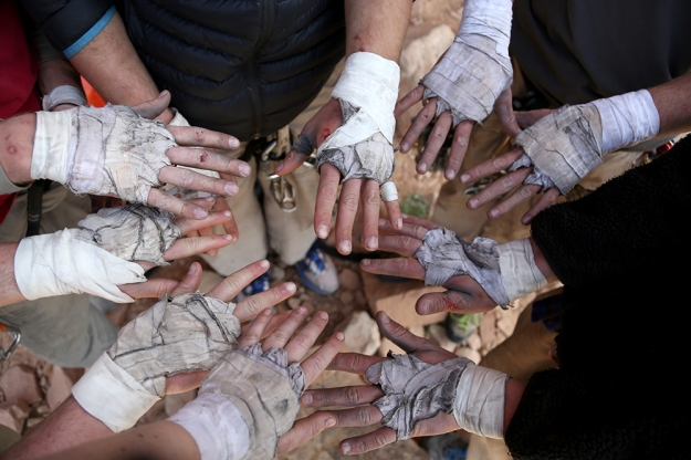 Climbers show off their hands wrapped in athletic tape after a week of climbing. Tape protects their hands from major scrapes while jamming hands in cracks.