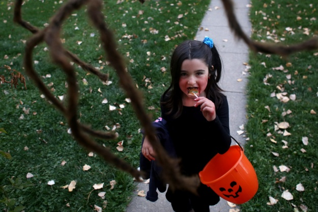 Ellie Feder eats candy on her way to another trick-or-treating destination on Oct. 31, 2014 in Paonia, Colo.
