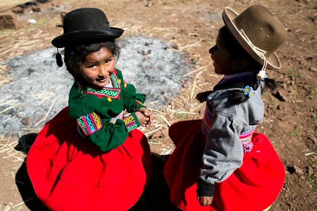 Girls twirl in their wool polleras in the village of Perka, Peru on the shore of Lake Titicaca.