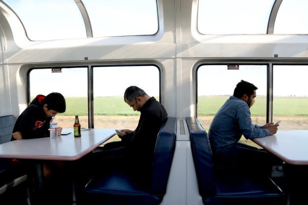 Passengers focus on their electronic devices while riding the train.
