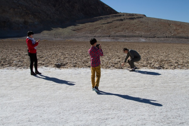 Chinese tourists Wen Hua Lee and Leo Liu Jun take pictures of their husband/father Jie Qi Liu in Death Valley National Park.