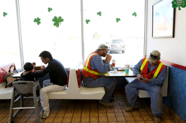 A family on a tour bus and local workers chow down in McDonald's on Interstate 5 in California.