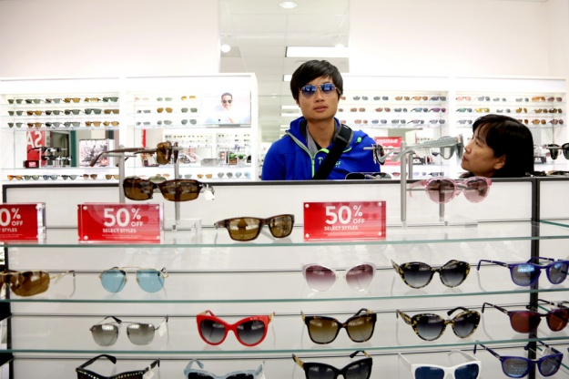 Henry Lu tries on sunglasses in Sunglass Hut at the Tanger Outlets in Barstow, Calif. Seventy percent of the store's paying customers arrive on Asian tour buses.