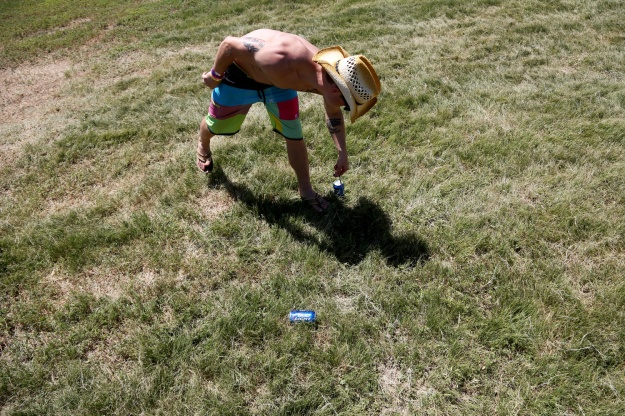 "Josh Kennedy, 24, extracts a dart from a punctured beer can while playing ""beer darts"" in the campground at Bands in the Backyard on June 19, 2015."