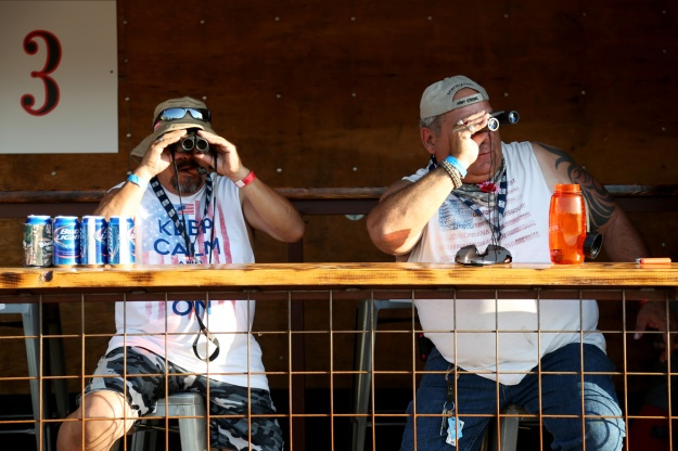 Joe Quesada and John Downey use binoculars to people watch and improve their view of the stage at Bands in the Backyard on June 19, 2015.
