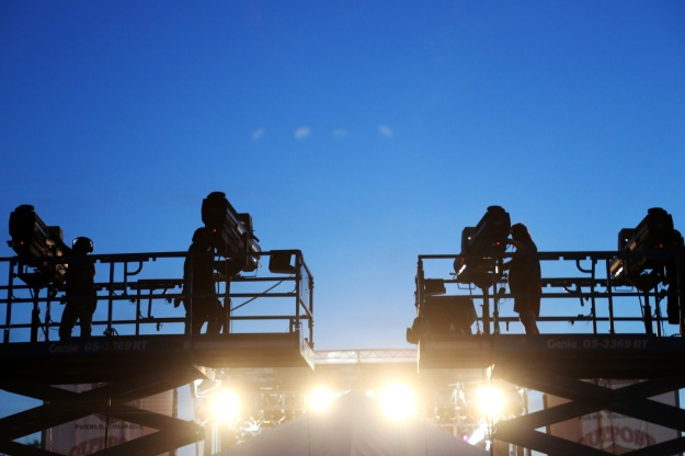 Technicians adjust spotlights as the sun sets at Bands in the Backyard on June 19, 2015.