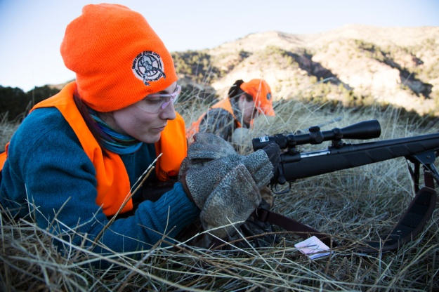 Laura Palmisano adjusts her grip on her rifle while waiting for dusk, the time when elk are most active.